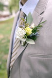 Boutonniere of white and yellow flowers with greens on lapel of a gray jacket. Close-up photo Stock Photos