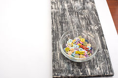 Boutons colorés dans la tasse en verre sur le vieux conseil en bois Images libres de droits