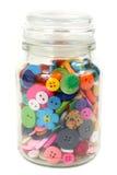 Boutons colorés de mercerie dans un pot en verre Verticale sur le blanc Image stock