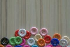 Boutons colorés multi sur la table en bois légère Photographie stock