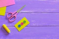 Boutons colorés sur le morceau de feutre de jaune Les ciseaux, fil, aiguille, feutre rapiècent sur un fond en bois avec l'espace  Images stock