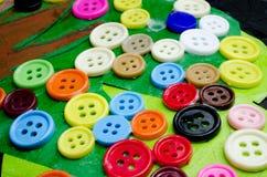 Boutons de beaucoup de couleurs collés sur le papier Photo stock