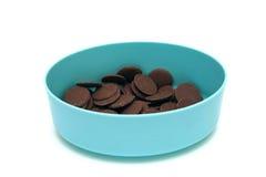 Boutons de chocolat au lait dans un récipient bleu Images stock