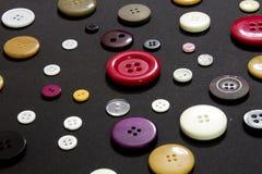 Boutons de couture colorés sur un fond noir Photographie stock libre de droits
