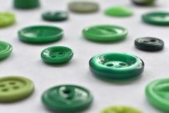Boutons de couture verts sur le blanc Photos stock