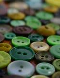 Boutons de couture verts sur une table en bois Photo stock
