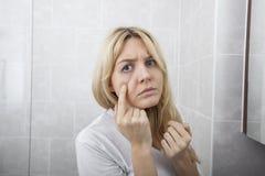 Boutons de examen de jeune femme sur le visage dans la salle de bains Photos libres de droits