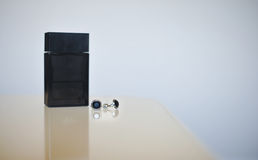 Boutons de manchette noirs de bouteille et d'argent de parfum d'isolement sur le fond gris Accessoires de mariage Photo libre de droits
