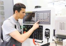 Boutons de pressing de travailleur sur la machine de commande numérique par ordinateur Photos stock