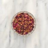Boutons de rose et pétales rouges écrasés secs dans une petite cuvette Images stock