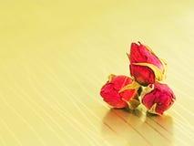 Boutons de rose sur un fond d'or photos stock