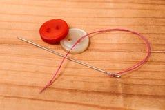 Boutons de tissu et aiguille de couture avec le fil rouge sur la table en bois Photos libres de droits