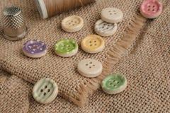 Boutons en bois avec des rayures de couleurs colorées sur un tissu rustique photos stock