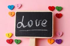 Boutons en forme de coeur avec amour de mot sur le tableau noir Fin de fond de jour du ` s de Valentine  Photographie stock