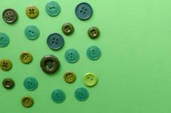 Boutons en plastique verts sur le fond de Livre vert Photos stock