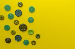 Boutons en plastique verts sur le fond de papier jaune Image libre de droits