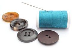 Boutons et bobine de couture de fil sur le fond blanc Photo stock