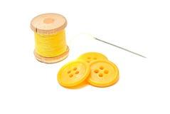Boutons et bobine de fil jaune Images stock