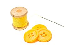 Boutons et bobine de fil jaune sur le blanc Photographie stock libre de droits