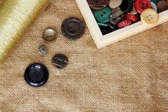 Boutons et bobine de fil sur le fond de toile de jute Photographie stock