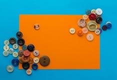Boutons et feuille de papier orange sur un fond bleu Photos stock