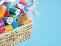 Boutons et fil de couture colorés dans une boîte en bois sur un fond bleu Photo libre de droits