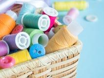 Boutons et fil de couture colorés dans une boîte en bois sur un fond bleu Photographie stock libre de droits