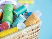 Boutons et fil de couture colorés dans une boîte en bois sur un fond bleu Images stock