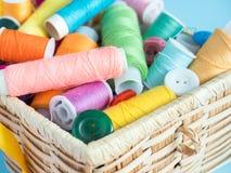 Boutons et fil de couture colorés dans une boîte en bois sur un fond bleu Image stock