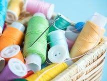 Boutons et fil de couture colorés dans une boîte en bois sur un fond bleu Images libres de droits