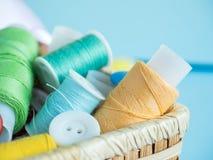 Boutons et fil de couture colorés dans une boîte en bois sur un fond bleu Photos stock