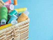 Boutons et fil de couture colorés dans une boîte en bois sur un fond bleu Photographie stock