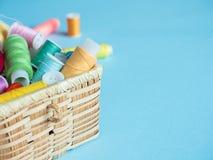 Boutons et fil de couture colorés dans une boîte en bois sur un fond bleu Photos libres de droits