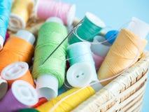 Boutons et fil de couture colorés dans une boîte en bois sur un fond bleu Photo stock