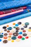 Boutons et tissu colorés sur le fond blanc Photo libre de droits