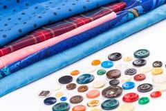 Boutons et tissu colorés sur le fond blanc Photo stock