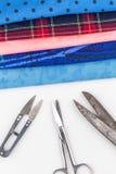 Boutons et tissu colorés sur le fond blanc Photographie stock