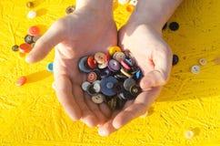 Boutons multicolores dans des mains Fond jaune couture, passe-temps, créatif, antiquités Photo libre de droits