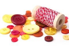 boutons rouges et oranges et fils de coton rouges sur b blanc Photos stock