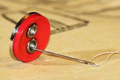 Boutons rouges sur le modèle de papier, thème de couture Images stock