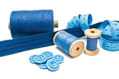 Boutons, tirette bleue et bobines de fil Photographie stock