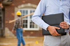 Bouw: Agent Holding Portfolio met Arbeider op Achtergrond Stock Fotografie