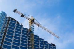 Bouw - de nieuwe blauwe glasbouw en kraan Stock Afbeelding