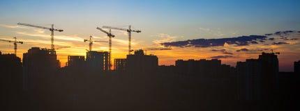 Bouw in de stralen van zonsondergang de silhouetten van torenkranen over verbazende zonsonderganghemel stock foto