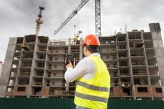 Bouw digitale tablet houden en inspecteur die buildin inspecteren royalty-vrije stock fotografie
