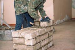Bouw een muur van bakstenen De studenten leren om bakstenen te leggen De bakstenen van de cementband De spatel tamped cement Bero royalty-vrije stock afbeeldingen