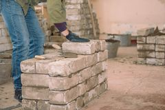 Bouw een muur van bakstenen De studenten leren om bakstenen te leggen De bakstenen van de cementband De spatel tamped cement Bero royalty-vrije stock foto's