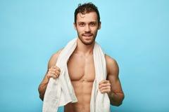 Bouw goed de ontzagwekkende gelukkige knappe mens met een handdoek rond hals stock foto