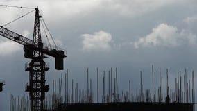 Bouw-kranen, de hemel van de wolkendekking, de bouwhigh-rise, Huissilhouet Bouwvakker die aan dak werkt stock footage