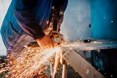 Bouw mannelijke arbeider die elektrohoekmolen voor scherpe ijzerbars met behulp van stock foto
